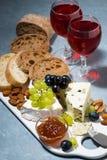 Ostplatta, ciabatta, nya druvor och två exponeringsglas av rött vin royaltyfri bild