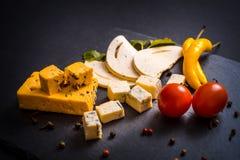 Ostplatta med ädelost, brien, tryffelhårdost med druvor, fikonträd, päron, honung, smällare, torkade frukter och muttrar på tabel Arkivbilder