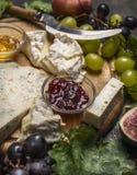 Ostplatta med gorgonzola, camembertdriftstopp och honung, druvor, persika på träskärbrädaslut upp Royaltyfria Foton