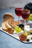 ostplatta, ny ciabatta, druvor och två exponeringsglas av rött vin royaltyfria bilder