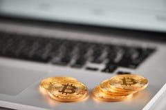 Ostra ostrość na złotych bitcoins umieszczających na srebnym laptopie z zamazaną pieniężną mapą na swój ekranie Zdjęcia Stock