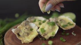 Ostras abiertas de la porción del primer de la cámara lenta con queso, la cebolla verde y el zumo de lima en un restaurante metrajes