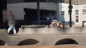 OSTRAVA, RÉPUBLIQUE TCHÈQUE, LE 28 AOÛT 2018 : Homme sans abri d'émotion authentique endormi sur un banc et un peuple de marche photos libres de droits