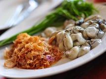 Ostrica fresca servita con aglio e le verdure Immagini Stock