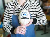Ostrich's egg with eyes and moustaches. Royalty Free Stock Photography