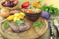 Ostrich steak with crispy baked potatoes and parsley Stock Photos