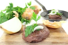 Ostrich steak with onions and parsley Royalty Free Stock Photos