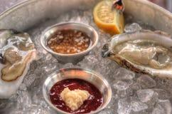 Ostriche crude su ghiaccio con le salse ed il limone fotografia stock