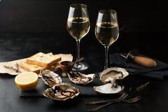 Ostriche fresche con il limone ed i bicchieri di vino Fotografia Stock Libera da Diritti