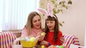 Ostrożna matka trzyma Wielkanocnego jajko, i jej córka z uśmiechem na twój twarzy z twój palcami zamaczającymi w farbie stawia zbiory