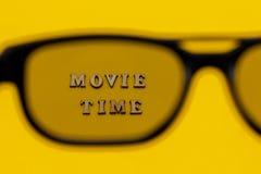 Ostrość na teksta filmu czasie przez 3D szkieł na koloru żółtego papieru tle Pojęcie rozrywka i zdjęcie stock