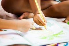 Ostrość na dziecko ręce trzyma kredkę maluje jej obrazek Obraz Royalty Free