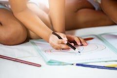 Ostrość na dziecko ręce trzyma kredkę maluje jej obrazek Fotografia Stock