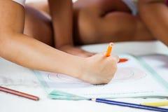 Ostrość na dziecko ręce trzyma kredkę maluje jej obrazek Zdjęcie Royalty Free