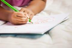 Ostrość na dziecko ręce trzyma kredkę maluje jej obrazek Obraz Stock