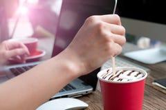 Ostrość na kobiety ręce miesza coffee/miękką część Fotografia Stock