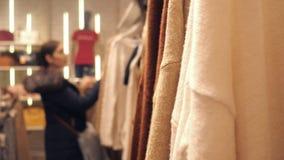 Ostrość na pulowerze zamazany tło młoda dziewczyna wyboru rzeczy zdjęcie wideo