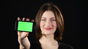 Ostrość na telefonie komórkowym Młodych kobiet ręki pokazuje pustego smartphone ekran odizolowywającego na zielonym tle i wskazuj zbiory wideo