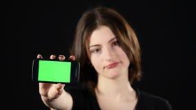 Ostrość na telefonie komórkowym Młodych kobiet ręki pokazuje pustego smartphone ekran odizolowywającego na zielonym tle i wskazuj zdjęcie wideo