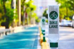 Ostrość roweru pasa ruchu znaka słup wewnątrz z zielonym drzewnym tłem Zdjęcia Stock
