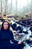 Ostrości młoda piękna dziewczyna robi joga pozie lotosowemu obsiadaniu w skale na rzece Medytuje w lesie z światłem słonecznym obraz royalty free