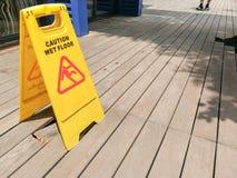 Ostrożność mokry podłogowy znak ostrzegawczy z zamazanym na drewnianej podłoga fotografia stock