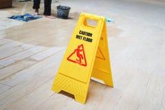 Ostrożność mokry podłogowy znak ostrzegawczy z zamazanym pracownikiem fotografia stock