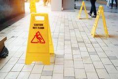 Ostrożność mokry podłogowy znak ostrzegawczy z zamazanymi ludźmi fotografia royalty free