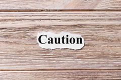 OSTROŻNOŚĆ słowo na papierze Pojęcie Słowa ostrożność na drewnianym tle Obraz Stock