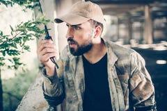 Ostrożny hireling opowiada przenośny radio trzymać je w prawej ręce Jest przyglądającym bezpośrednim outside od Obrazy Royalty Free