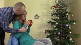 Ostrożny mężczyzna daje kobiety filiżanki kawy herbacianego pobliskiego Bożenarodzeniowego jedlinowego drzewa zbiory wideo