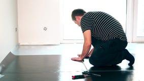 Ostrożny męski pracownika mężczyzna kłaść leżeć u podłoża dla laminat podłoga instalaci zbiory