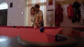 Ostrożny młody człowiek uczy się jego dziewczyny bawić się basenu salowego w pubie - zbiory wideo