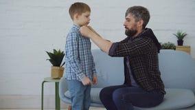 Ostrożny ojciec pomaga jego małego syna dostawać ubierającym, zapina jego koszula i smooting włosy, Kochający rodzic, szczęśliwy zdjęcie wideo