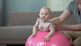 Ostrożny ojciec robi sprawności fizycznej ćwiczy na dużej piłce z śliczną małą dziewczynką zbiory