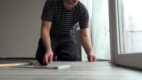 Ostrożny rzemieślnika mężczyzna instaluje drewnianego laminata podłogową deskę w domu zbiory