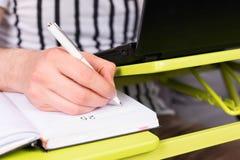 Ostrość na man& x27; s ręki writing w dzienniczku Zdjęcia Royalty Free