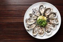 Ostron i en platta på en brun träbakgrund, skaldjur fotografering för bildbyråer
