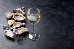 Ostron med citronen och vitt vin arkivbild