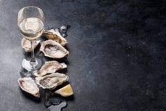 Ostron med citronen och vitt vin arkivfoto