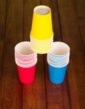 Ostrosłup kolorowe rozporządzalne papierowe filiżanki na tło zmroku drewnie Fotografia Stock