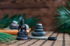 Ostrosłupy szarzy zen kamienie z zielonymi liśćmi i Buddha statuą Pojęcie harmonia, równowaga i medytacja, zdrój, masaż, relaksuj fotografia royalty free