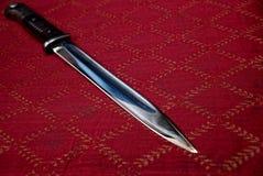 Ostry bagneta nóż na czerwonym płótnie Obrazy Royalty Free
