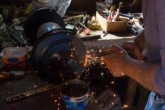 Ostrzący ścinaka na szlifierskiej maszynie z iskrami lata Fotografia Stock