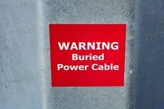Ostrzegać Zakopującego władza kabla znaka na metalu słupie Obraz Royalty Free
