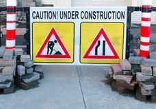 Ostrzegawczy deska z inskrypcj ostrożnością, W budowie przy remontowym miejscem chodniczek lub droga Obrazy Stock