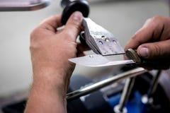 Ostrzyć łowieckiego nóż na specjalnym wyposażeniu fotografia royalty free