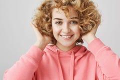 Ostrzyżenia i stylu życia pojęcie Ślicznej eleganckiej z włosami kobiety wzruszający włosy podczas gdy ono uśmiecha się szeroko i obrazy royalty free