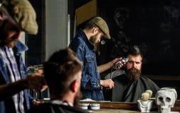 Ostrzyżenia pojęcie Fryzjer męski z włosianym cążki pracuje na fryzurze dla mężczyzna z brodą, zakładu fryzjerskiego tło Fryzjera obrazy royalty free