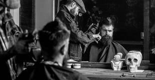 Ostrzyżenia pojęcie Fryzjer męski z włosianym cążki pracuje na fryzurze dla mężczyzna z brodą, zakładu fryzjerskiego tło Modnisia obrazy royalty free